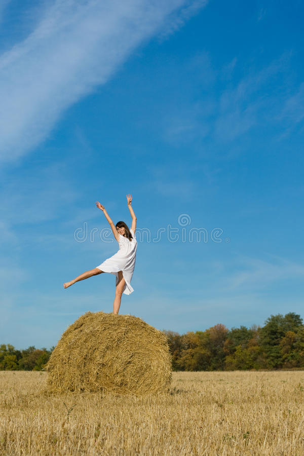 Jolie fille dans la robe blanche sur la meule de foin dans le domaine   photo libre de droits