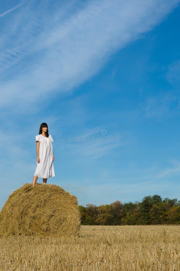 Jolie fille dans la robe blanche sur la meule de foin dans le domaine photos libres de droits