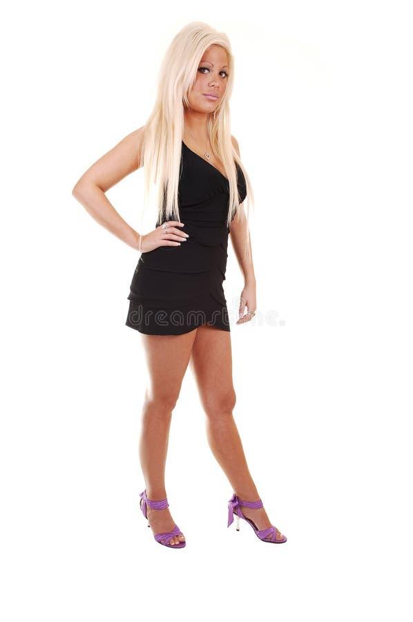 Jolie fille dans la robe courte noire. photographie stock