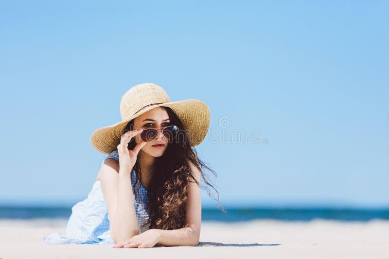 Jolie fille dans le chapeau de paille s'étendant sur la plage sablonneuse photos stock