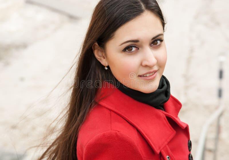 Jolie fille dans le manteau rouge sur l'air de plein image libre de droits