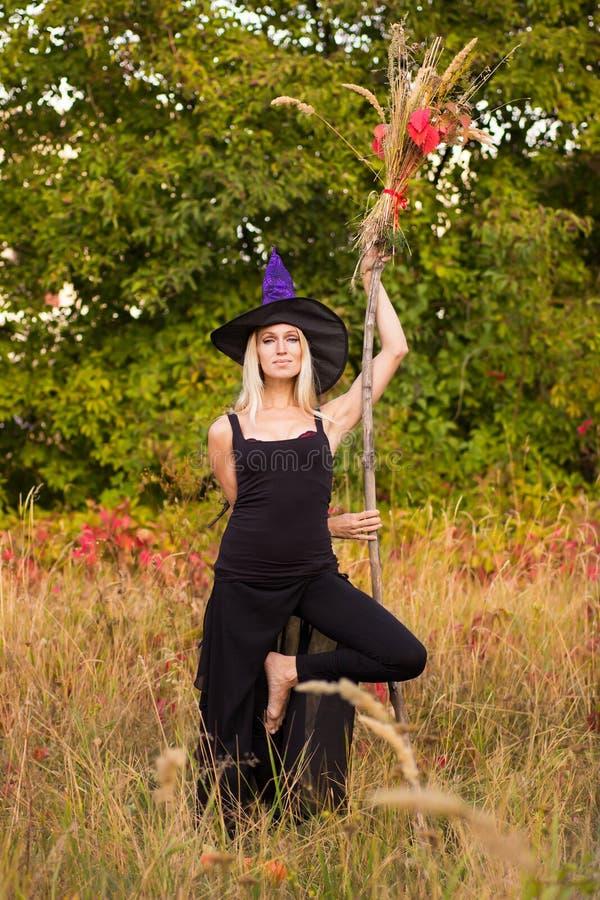 Jolie fille dans le yoga de pratique de costume de sorcière images stock