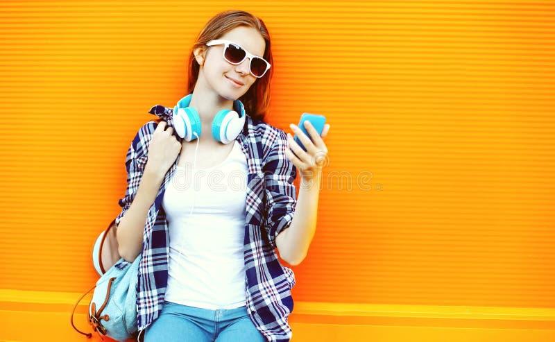 Jolie fille dans les lunettes de soleil et des écouteurs utilisant le smartphone images stock