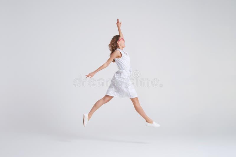 Jolie fille dans sauter de robe d'isolement au-dessus du fond image libre de droits