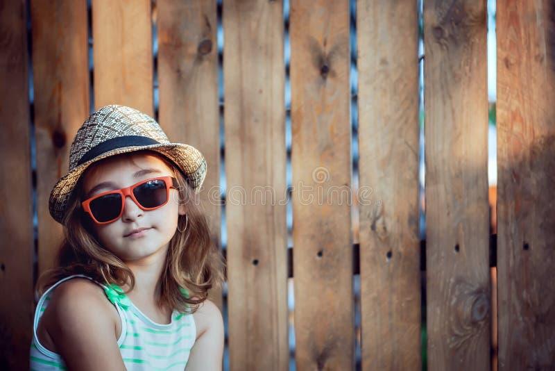 Jolie fille dans un chapeau sur fond brun image stock