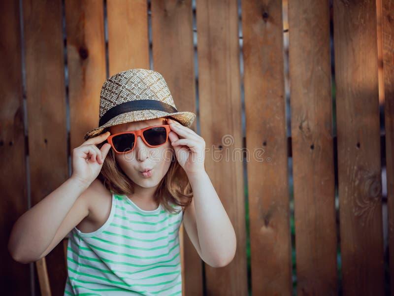 Jolie fille dans un chapeau sur fond brun photos stock