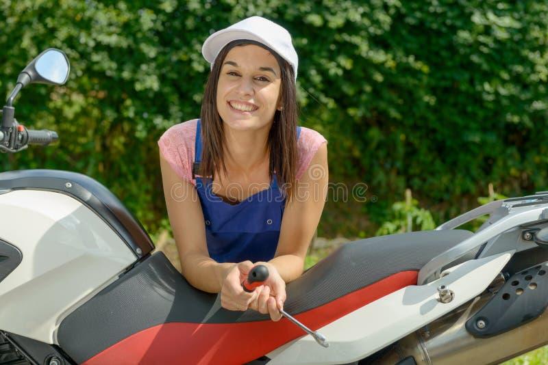 Jolie fille de brune dans la mécanique de motocyclette image libre de droits