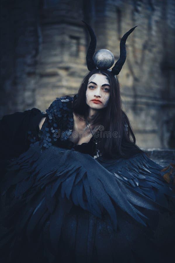 Jolie fille de démon avec les ailes noires derrière son dos, déesse d'un autre monde au-delà, ange de noir de Halloween photos stock