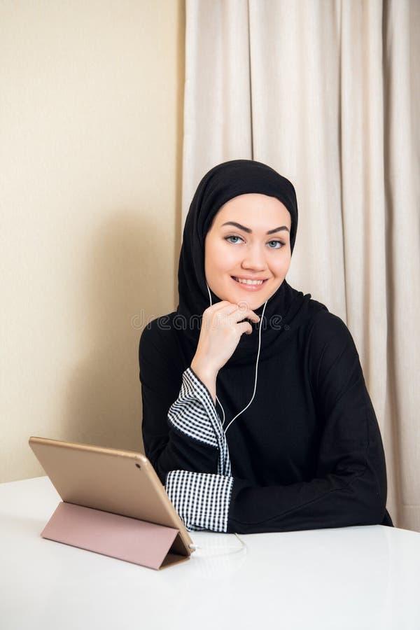 Jolie fille de l'adolescence Arabe à l'aide de la tablette dans la salle de classe de lycée photos stock