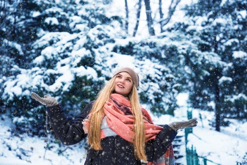 Jolie fille de l'adolescence marchant en parc de ville au temps de neige image libre de droits