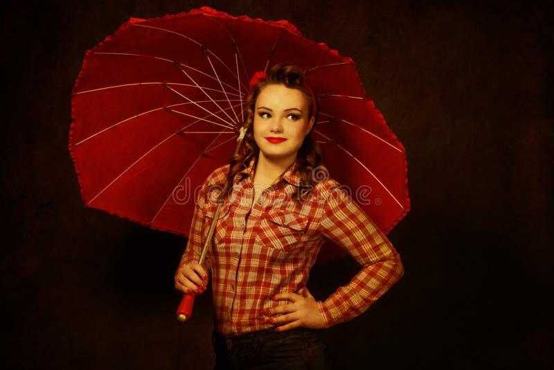 Jolie fille de pin-up dans le rétro style du ` s du vintage 50 avec le parapluie rouge illustration stock