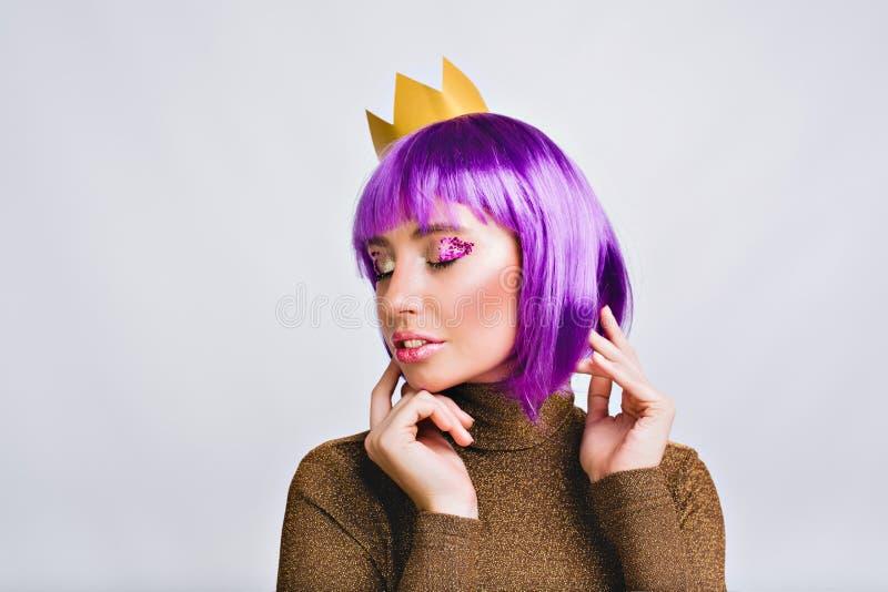 Jolie fille de portrait avec la coiffure pourpre dans la couronne d'or dans le studio Elle semble paisible, a la tresse violette  photos stock