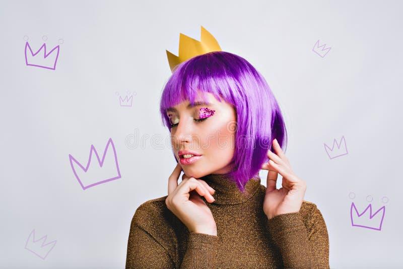 Jolie fille de portrait avec la coiffure pourpre dans la couronne d'or dans le studio Elle semble paisible, a la tresse violette  photos libres de droits
