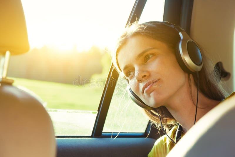 Jolie fille de sourire écoutant la musique avec des écouteurs se déplaçant dedans photos libres de droits