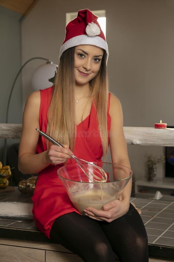 Jolie fille de sourire dans l'habillement de Noël se reposant sur la table et préparant le gâteau pour des pâtisseries photo stock
