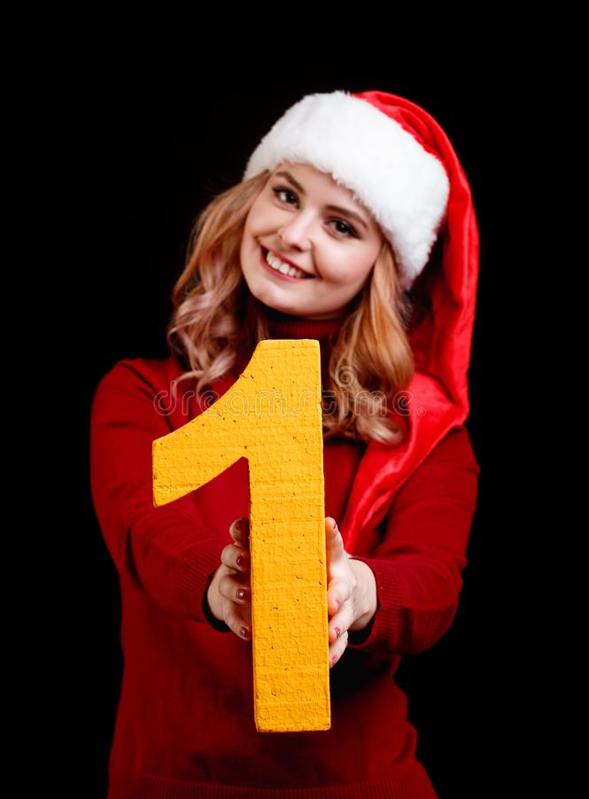 Jolie fille de sourire dans un chapeau de Noël tenant le numéro 1 sur un fond noir Concept 2018 de nouvelle année image libre de droits