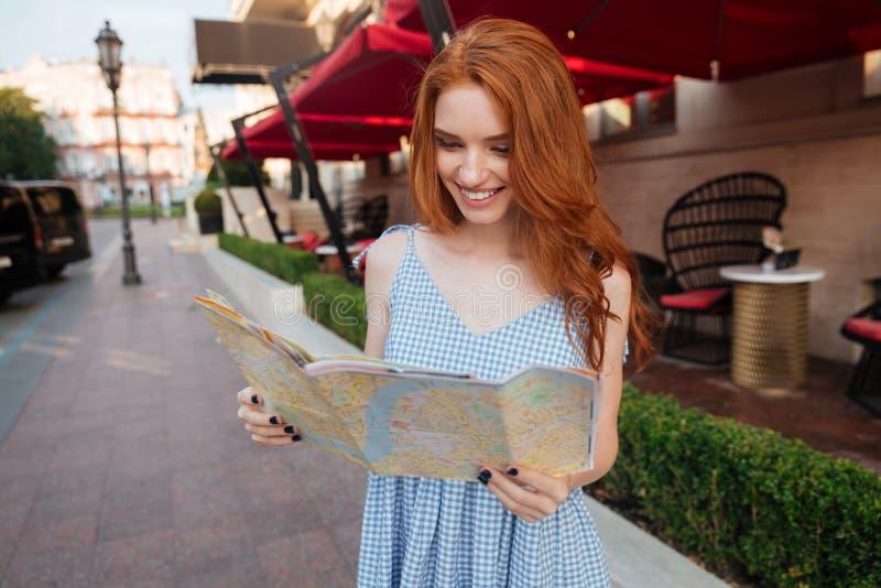 Jolie fille de sourire regardant la carte photographie stock libre de droits