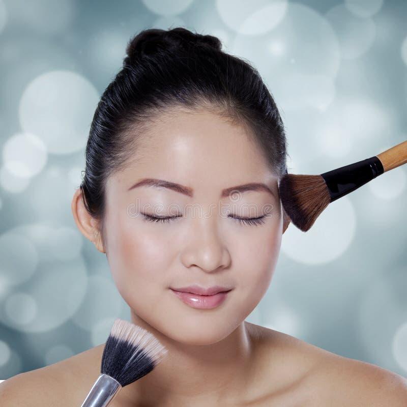Jolie fille employant des brosses de maquillage dans le studio photo stock