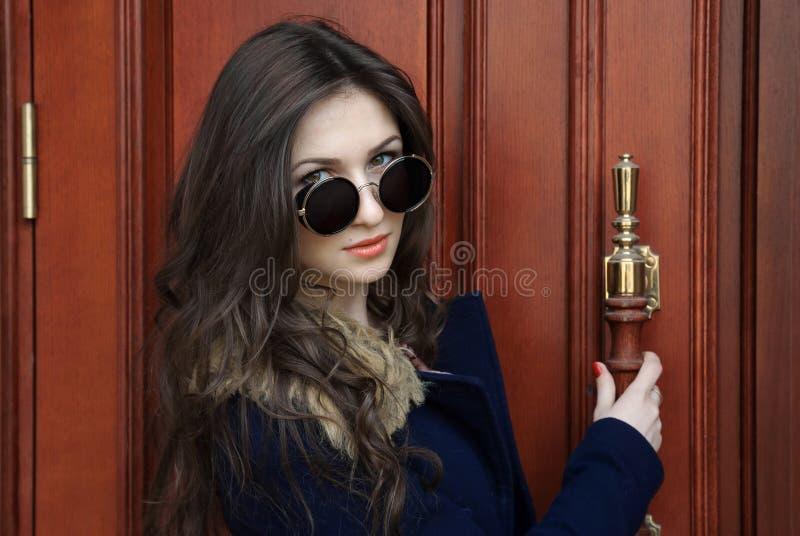 Jolie fille en manteau bleu et verres noirs photos stock