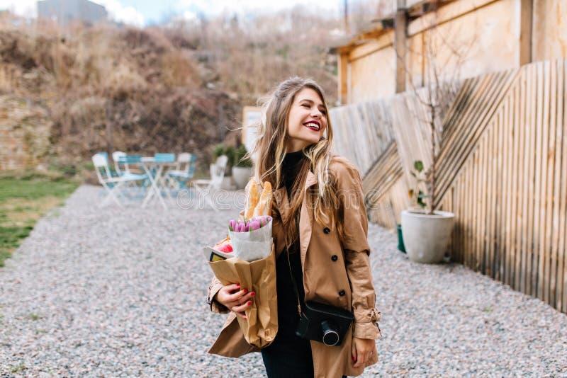 Jolie fille européenne blanche dans des retours bruns à la mode de manteau des achats avec des achats dans le sac de papier Jeune photographie stock libre de droits