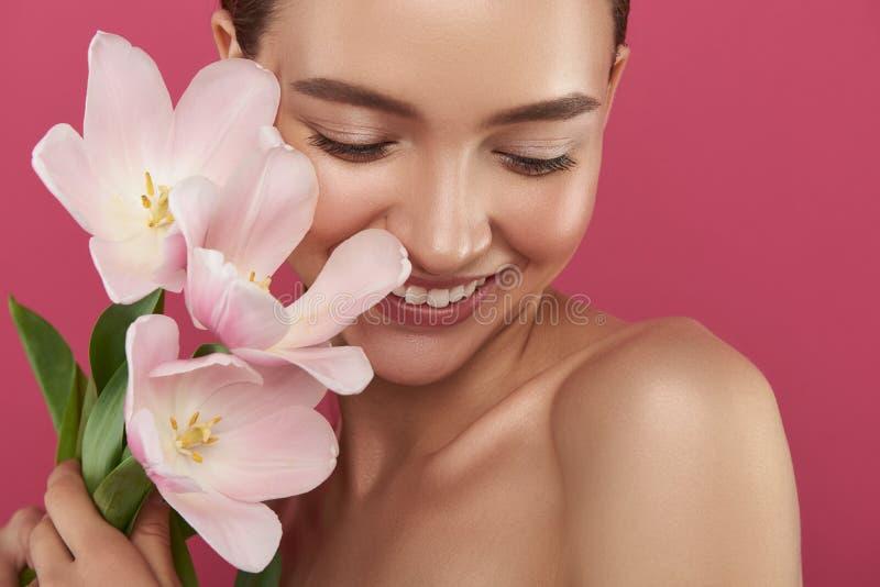 Jolie fille gaie avec les épaules nues tenant de belles tulipes image stock