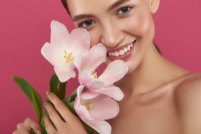 Jolie fille joyeuse avec les épaules nues tenant de belles tulipes image stock