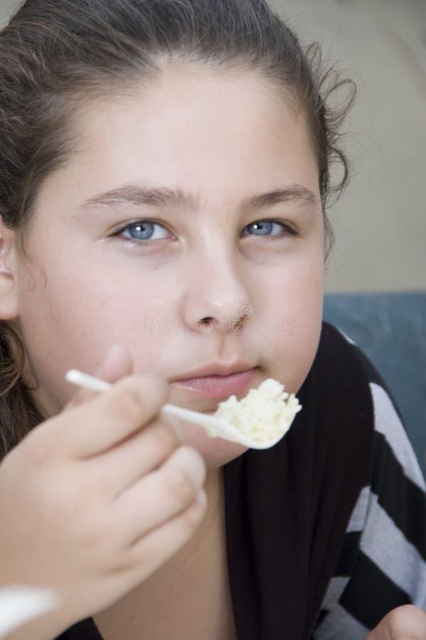 Jolie fille mangeant du riz images stock