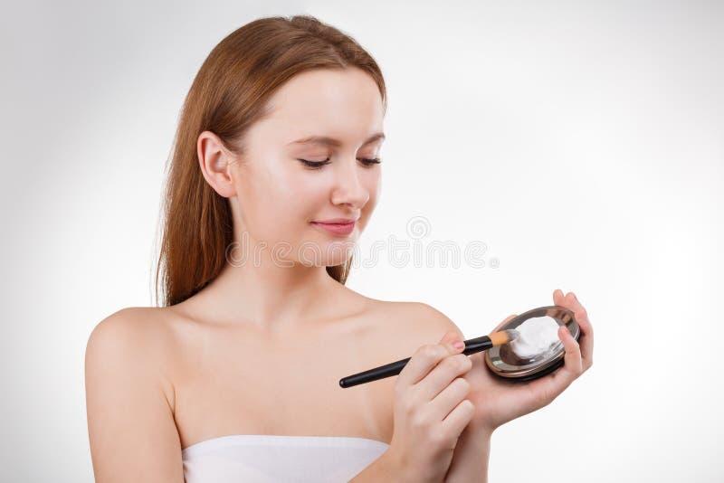 Jolie fille mettant la crème ou le masque faciale sur la jeune peau de visage avec la brosse du pot Cosmétologie, l'espace de cop photographie stock libre de droits