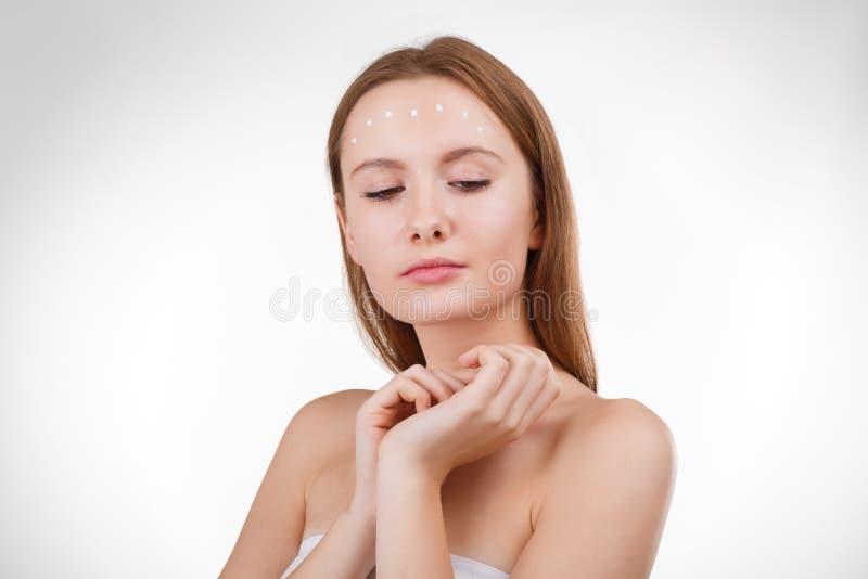 Jolie fille mettant la crème ou le masque faciale sur la jeune peau de visage avec ses doigts photo stock