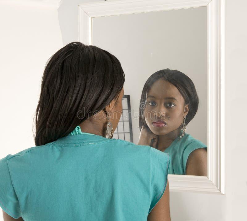 Jolie fille regardant dans un miroir photos libres de droits