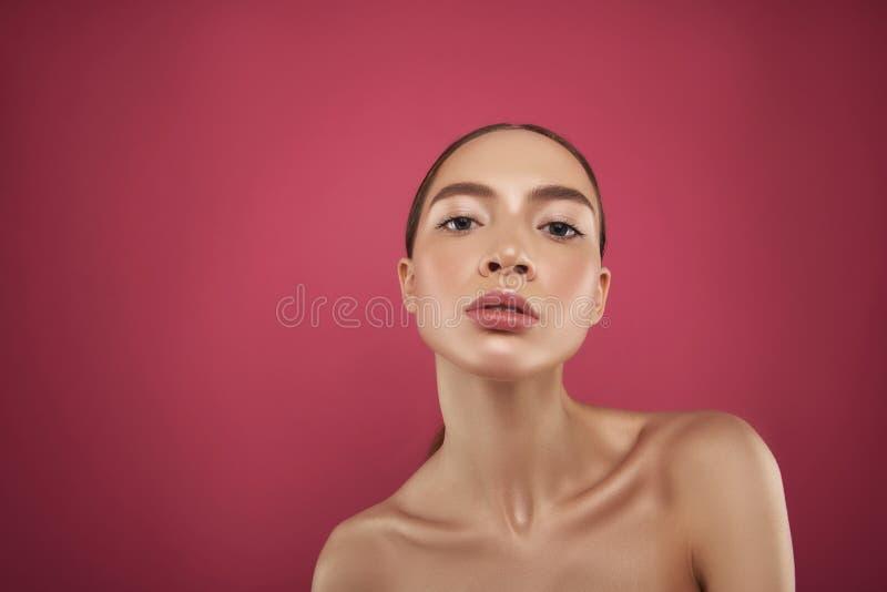 Jolie fille sûre avec le maquillage naturel se tenant sur le fond rose photos libres de droits
