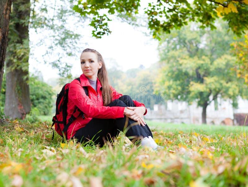 Jolie fille s'asseyant sur les feuilles d'automne photos libres de droits