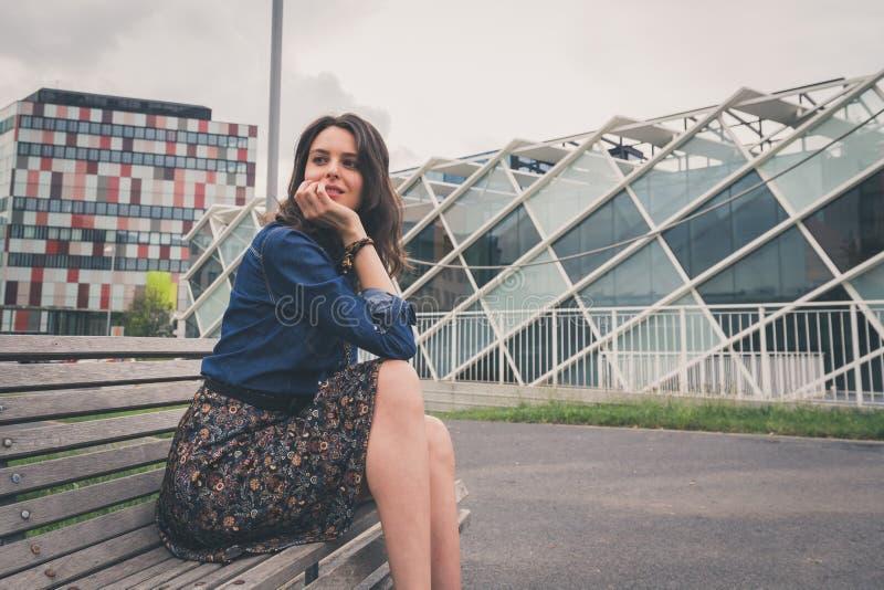Jolie fille s'asseyant sur un banc dans la rue images libres de droits