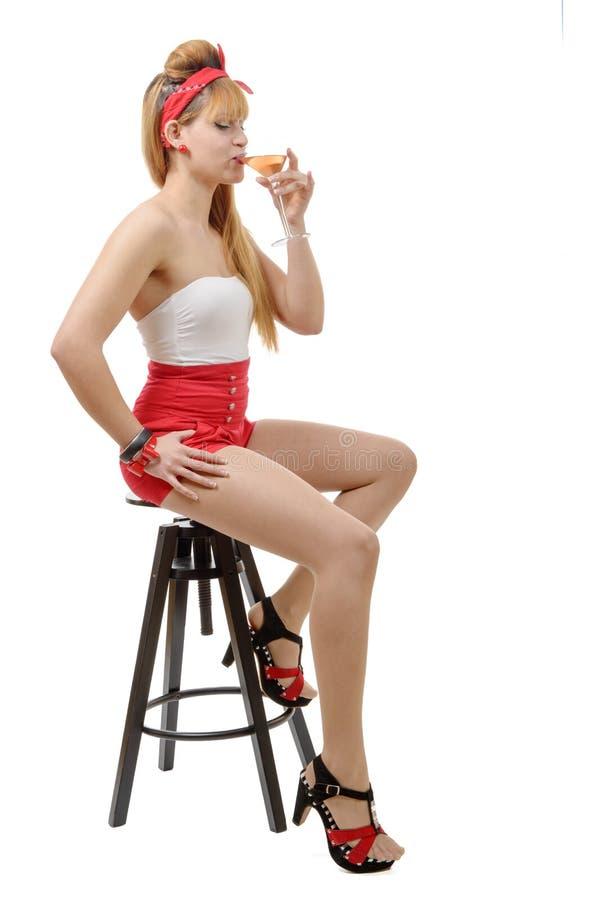 Jolie fille s'asseyant sur un tabouret, buvant un verre de vin photographie stock