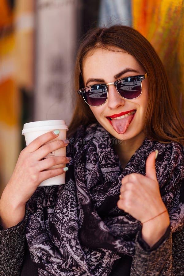 Jolie fille se tenant devant le mur avec la tasse de café photos libres de droits
