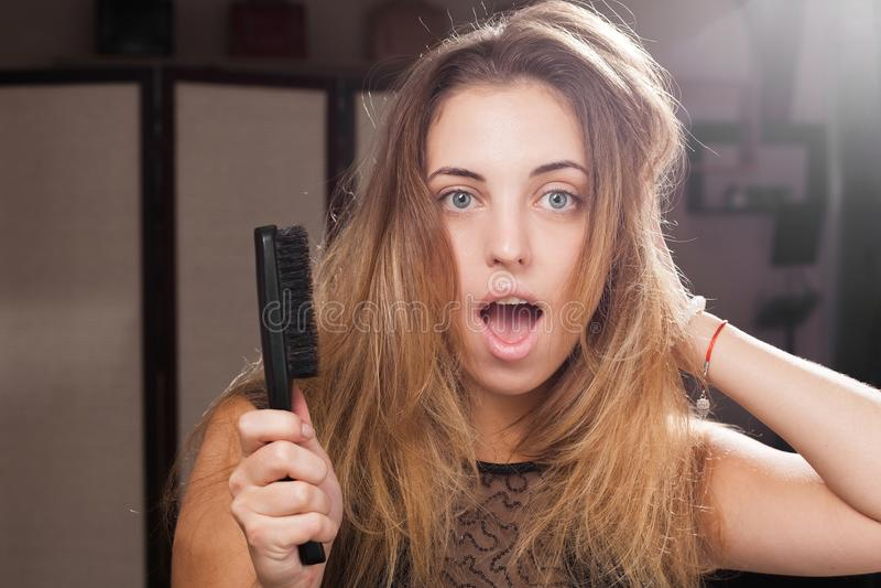 Jolie fille soumise à une contrainte touchant les cheveux en désordre débordants image stock