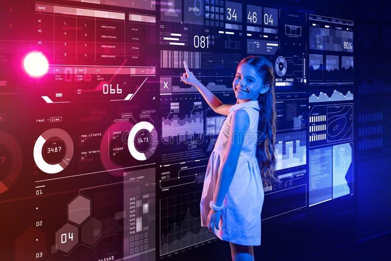 Jolie fille souriant et montrant son nouvel ordinateur futuriste image libre de droits