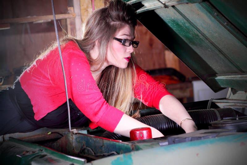 Jolie fille travaillant au moteur images stock