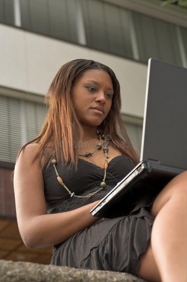 Jolie fille travaillant avec l'ordinateur portatif à l'extérieur photo stock