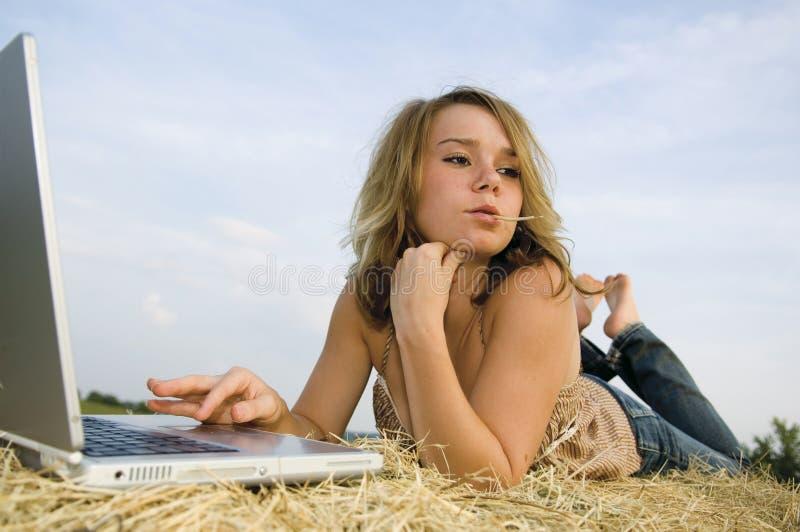 Jolie fille travaillant sur l'ordinateur portatif photos libres de droits