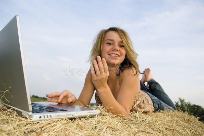 Jolie fille travaillant sur l'ordinateur portatif photo stock