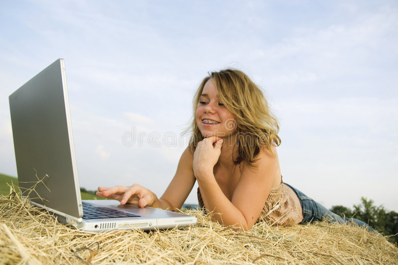 Jolie fille travaillant sur l'ordinateur portatif photos stock
