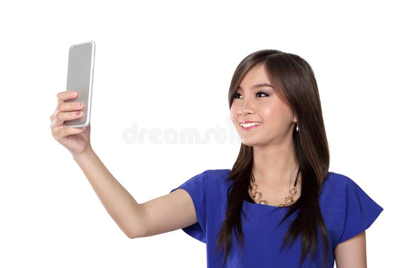 Jolie fille utilisant le téléphone portable pour l'appel vidéo, isolée en blanc images stock