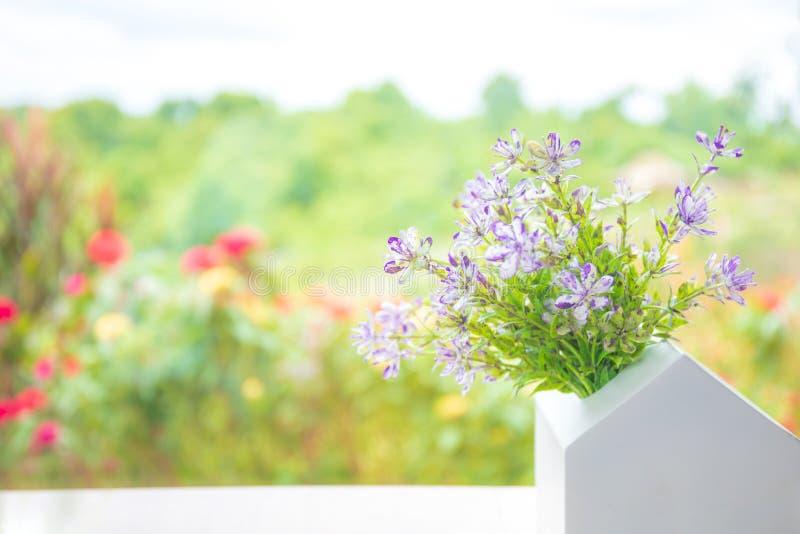 Jolie jolie fleur de fake colorée dans un pot blanc sur la table blanche avec espace de copie photo stock