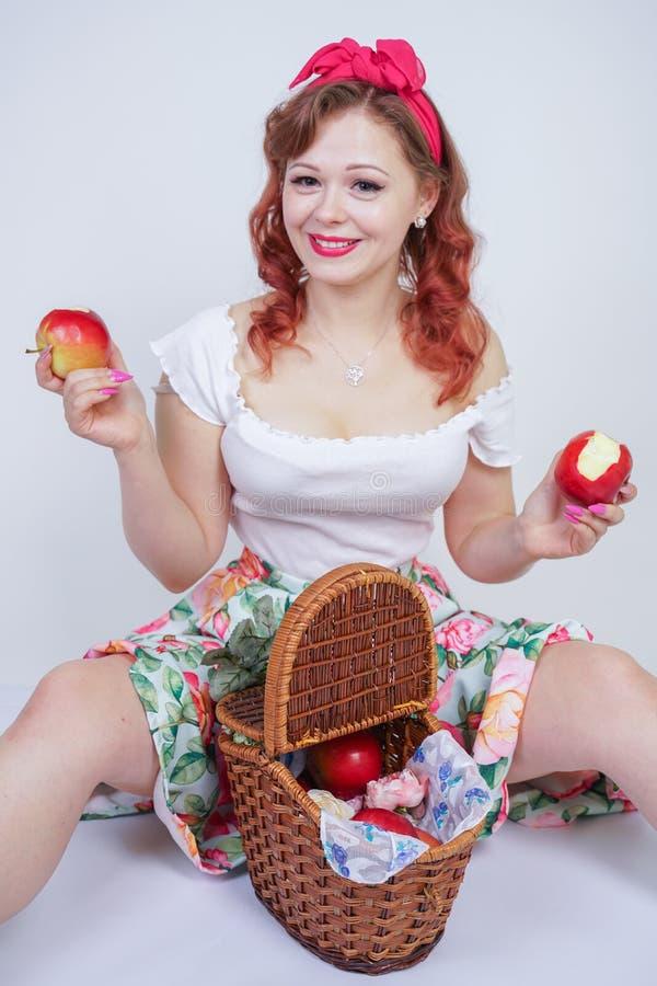 Jolie goupille vers le haut de la pose heureuse caucasienne de jeune fille avec les pommes rouges dame mignonne de cru dans la ré photos stock