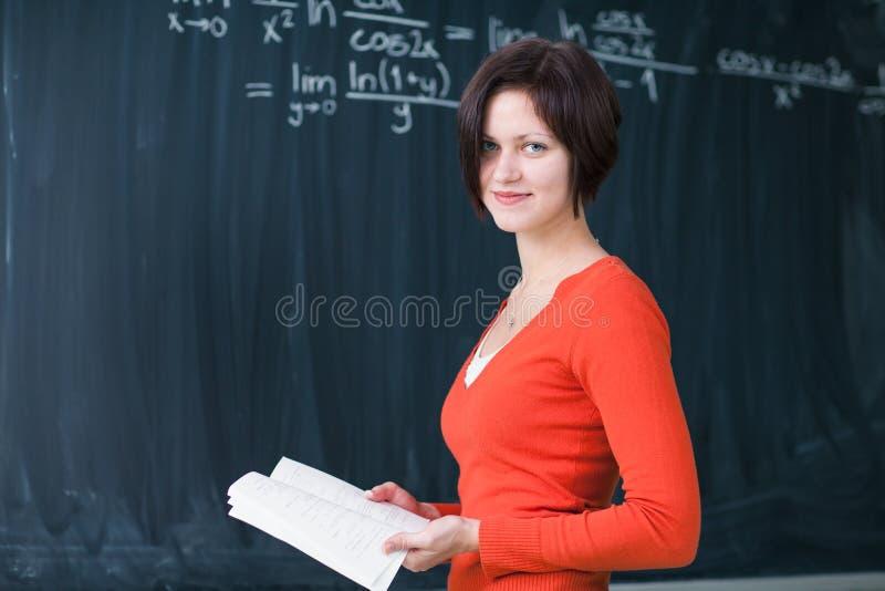 Jolie, jeune écriture d'étudiant universitaire sur le tableau image stock