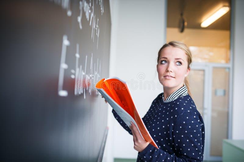 Jolie, jeune écriture d'étudiant universitaire sur le tableau/blackboa photographie stock libre de droits