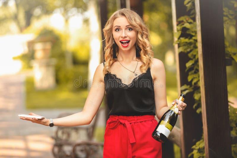 Jolie jeune étudiante caucasienne attirante qui rit joyeusement, parle au téléphone, tient une bouteille de champagne et appell photos libres de droits