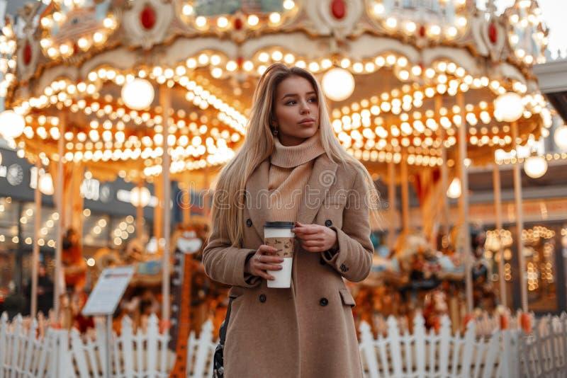 Jolie jeune belle femme dans un manteau élégant d'automne et un café potable de chandail tricoté par cru en parc de ville image libre de droits