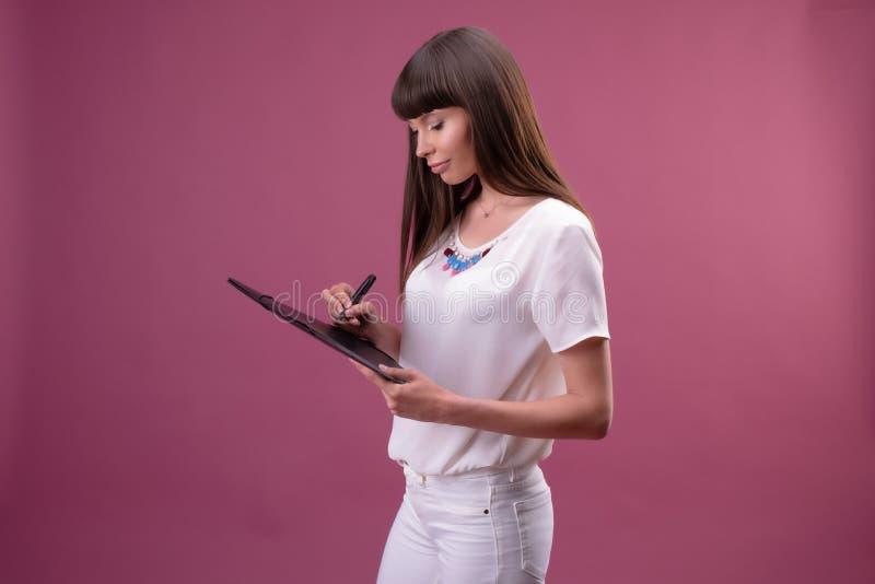 Jolie jeune belle position de femme, écriture, notes de prise, tenant l'organisateur de manuel à disposition et le stylo photographie stock libre de droits
